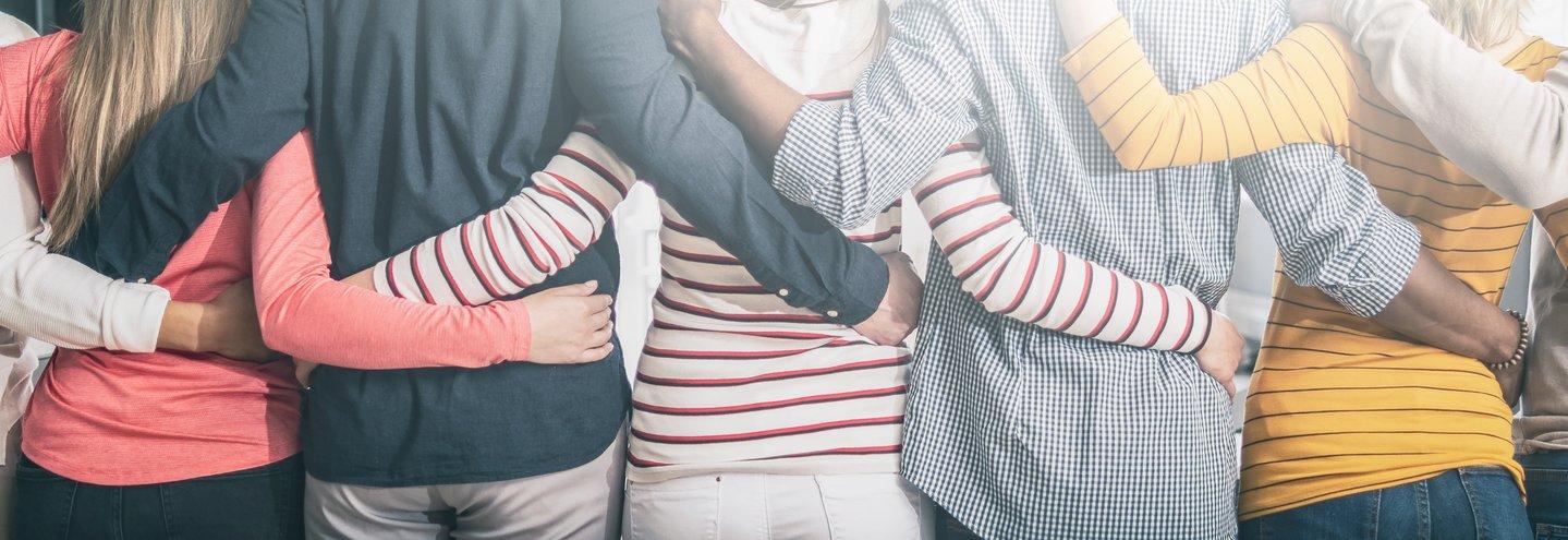 Das Foto zeigt sich umarmende Menschen.