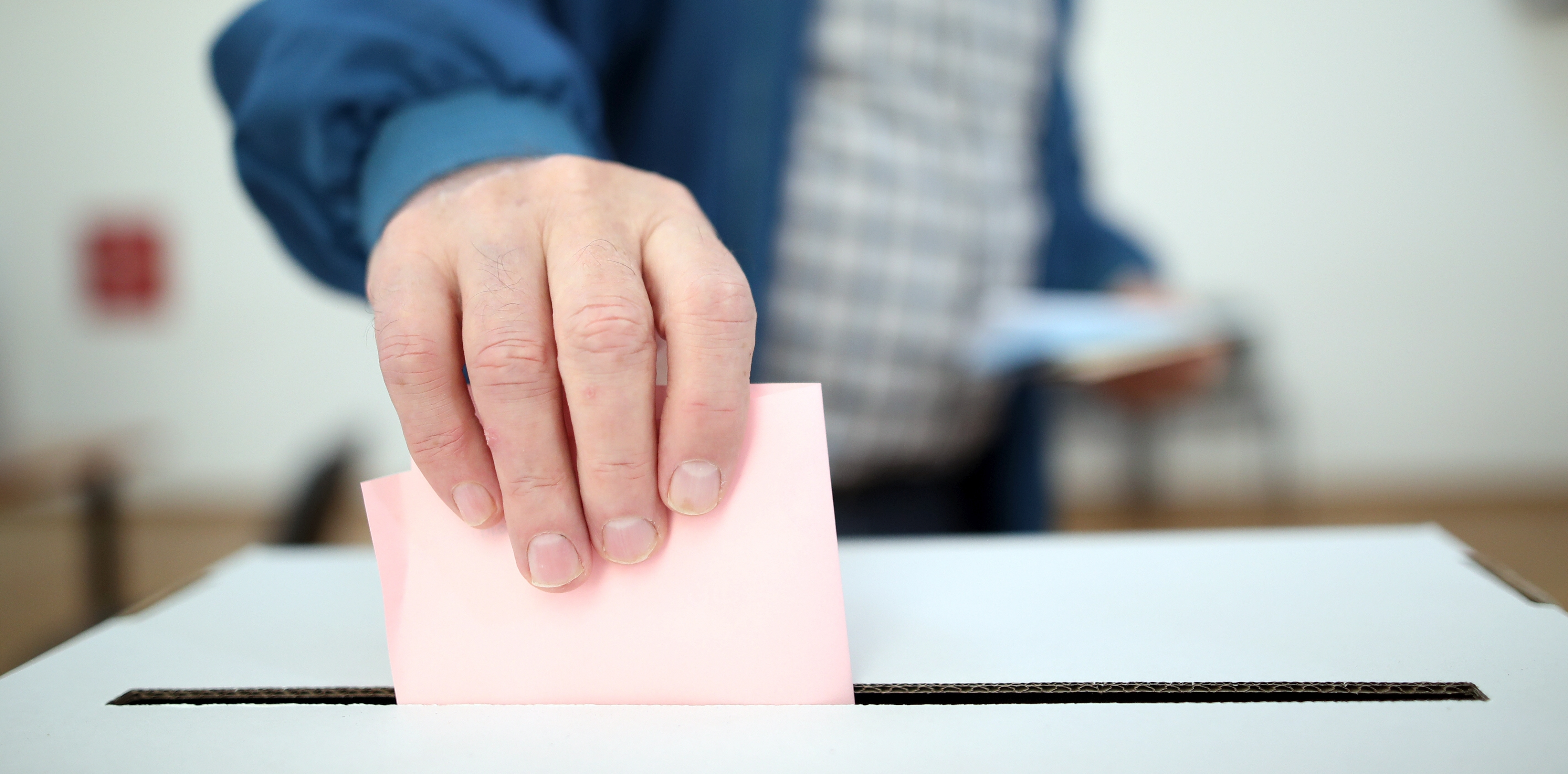 Ein Mann wirft einen Wahlzettel in eine Urne.